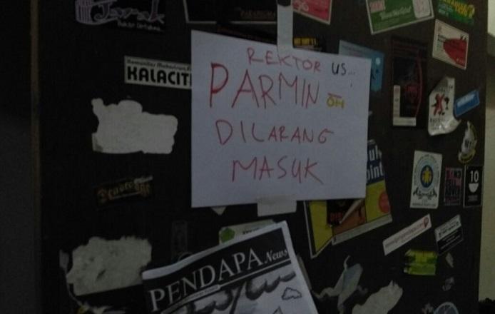 """Lembar bertuliskan """"Parmin Dilarang Masuk"""" tertempel di pintu kantor redaksi LPM Pendapa UST pada Kamis (17/11) - Arfrian/EKSPRESI"""